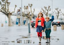 Portrait of two funny fashion kids. Two funny kids, little brother and sister playing together in a city under the rain in early spring. Chidren wearing rain Royalty Free Stock Photos