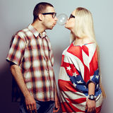 Portrait of two funny hipsters. Happy pregnancy concept: portrait of two funny hipsters (husband and wife) in trendy glasses and clothes playing with their stock photography