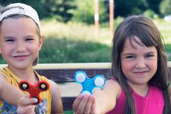 Portrait of two funny smiling friends playing with colorful fidget spinners on the playground. Popular stress-relieving Stock Image
