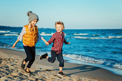 Portrait of two funny white Caucasian children kids friends playing running on ocean sea beach on sunset. Group portrait of two funny white Caucasian children Royalty Free Stock Photography