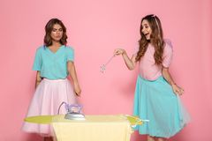 Portrait of a two funny young girls ironing clothes. On a pressboard while standing with an iron an a magical wand isolated over pink background Stock Photos