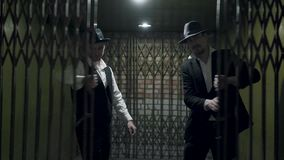 Portrait two gangsters men in formal suits and fedora hat opening a metal forged gates. Two serious gangsters men in formal suits and fedora hat opening a metal stock footage