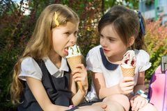 Portrait of two girlfriends schoolgirls 7 years old in school uniform with backpacks eating ice cream. Background city, summer, si. Dewalk, decorative bushes Stock Photography