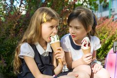 Portrait of two girlfriends schoolgirls 7 years old in school uniform with backpacks eating ice cream. Background city, summer, sidewalk, decorative bushes Stock Photo