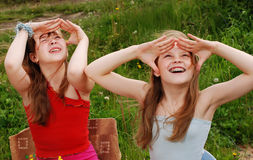 Portrait of two girls. Two girls talk about the secrets in the summer on a lawn stock photos