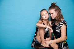 Portrait of two girls on a blue background royalty free stock image
