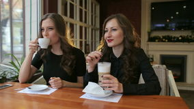 Portrait of two girls in a cafe with a coffee. Portrait of two luxurious girls with red lipstick sitting in a cafe and drink coffee in the winter stock video footage