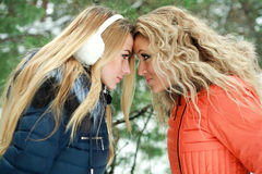 Portrait of two girls in conflict. Posing in pinewood, on a winter day Royalty Free Stock Photos