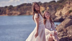 Portrait of two girls in dresses on the background of nature