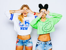 Portrait of two girls fashionable blonde and brunette hiding their eyes by hands. Showing perfect manicure. Wearing. White top and jeans shorts, with make up Stock Photography