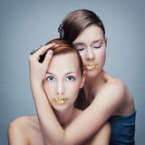Portrait of two girls with golden lips. Studio photo of two young women Royalty Free Stock Image