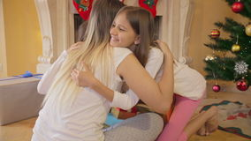 Portrait of two girls hugging mother after receiving Christmas gifts. Two girls hugging mother after receiving Christmas gifts stock footage