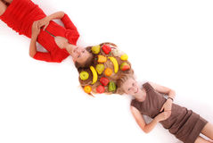 Portrait two girls with intertwined hairs and fruits Stock Photography