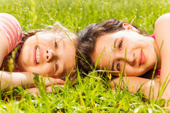 Portrait of two girls laying on grass together Stock Photography