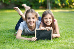 Portrait of two girls lying on grass with chalkboard Royalty Free Stock Image