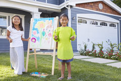 Portrait Of Two Girls Painting Picture In Garden Royalty Free Stock Photos