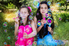 Portrait of two girls playing with bubble blower Stock Photo