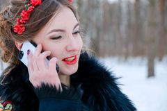 Portrait of two girls in Slavic style in the winter forest talking on a mobile device stock photography