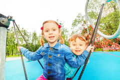 Portrait of two girls on swing set in summer Stock Photo
