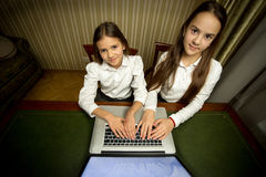 Portrait of two girls using laptop at cabinet Stock Images