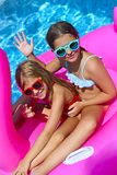 Portrait of two girls wearing sunglasses, happy friends on inflatable flamingo swim float. Enjoying pool party in summer stock photography
