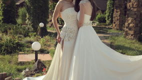 Portrait of two girls in wedding dresses and. Crowns outdoors in the park stock video