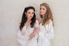 Portrait of two girls in white dresses wedding. Portrait of two girls in white dresses blonde and bojunetka wedding Royalty Free Stock Photos