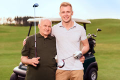 Portrait of two golfers on cart background. Granddad and grandson. Portrait of two smiling golfers holding golf clubs on background of cart on course Royalty Free Stock Image