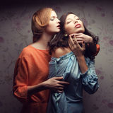Portrait of two gorgeous girlfriends in blue and orange dresses Stock Photos