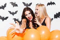 Portrait of two gothic beautiful young women with orange balloons Stock Images
