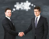 Teamwork and friendship concept. Portrait of two handsome smiling businessmen with abstract puzzle drawing shaking hands on chalkboard background. Teamwork and Stock Photo