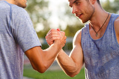 Portrait of two handsome strong men handshake. Focused on hands. Portrait of two handsome strong men handshake outdoors on summer day. Focused on hands Stock Photography