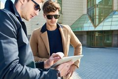 Two Handsome Businessmen Using Tablet Outdoors. Portrait of two handsome young businessmen wearing sunglasses using digital tablet and chatting during coffee Stock Photos