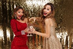 Portrait of two happy attractive girls in shiny dresses. Pouring champagne into glasses while standing and celebrating isolated over golden shiny background Royalty Free Stock Images