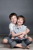 Portrait of two happy brothers on agray background Stock Photo