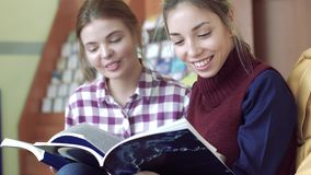 Portrait of two happy female students reading in library stock video footage