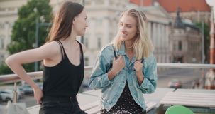 Beautiful young girls relaxing on a rooftop in a city. stock footage