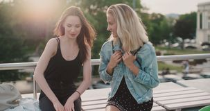 Beautiful young girls relaxing on a rooftop in a city. stock video footage