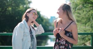 Portrait of two happy girls discussing latest gossip news. Two young girls in a city enjoying summer. Positive face expressions, emotions, feelings, body Stock Image