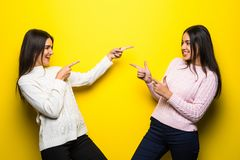 Portrait of two happy girls dressed in sweaters pointing fingers each other isolated over yellow background. Portrait of two happy girls dressed in sweaters Royalty Free Stock Photography