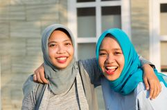 Portrait of two happy hijab women, smiling at the camera while embracing in front of their house royalty free stock photography