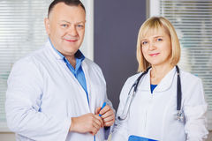 Portrait of two happy mature doctors. Stock Photos