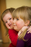 Happy young sisters. Portrait of two happy preschool sisters cuddling or hugging royalty free stock images