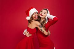 Portrait of two happy pretty girls in christmas dresses. Hugging and looking at camera isolated over red background Royalty Free Stock Image