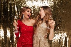 Portrait of two happy pretty girls in shiny dresses. Holding glasses with champagne while looking at each other and celebrating isolated over golden shiny Stock Photos