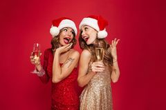 Portrait of two happy pretty girls in shiny dresses. Holding glasses with champagne while looking at each other and celebrating isolated over golden shiny Royalty Free Stock Photo
