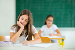 Portrait of two happy schoolgirls in a classroom Stock Image