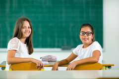 Portrait of two happy schoolgirls in a classroom Royalty Free Stock Photography