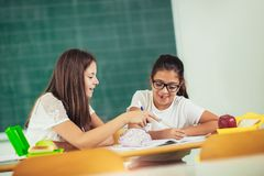 Portrait of two happy schoolgirls in a classroom Stock Image