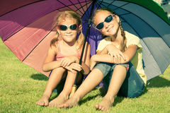 Portrait of two happy sister sitting on the grass Royalty Free Stock Photos